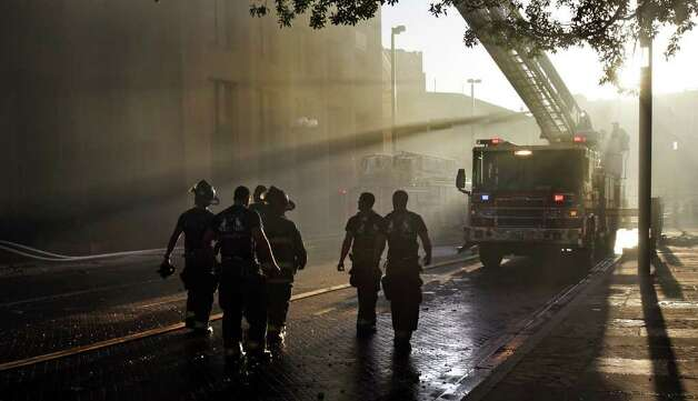 San Antonio Fire Fighters walk back to their truck as the sun comes up at the scene of a massive fire which destroyed Main Street Ballroom, Poblano's Restaurant and Meat Market Barbeque Restaurant at Main Plaza. Saturday, Oct. 1, 2011. Photo: BOB OWEN, SAN ANTONIO EXPRESS-NEWS / rowen@express-news.net