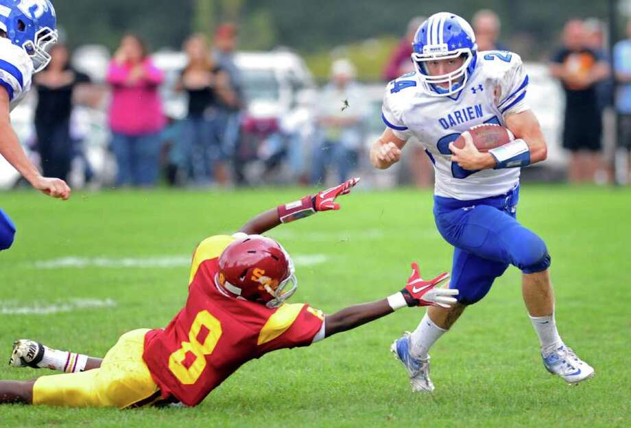 Darien's Corey Eppley escapes the grasp of St. Joseph's Darren Jackson during Saturday's game at the St. Joseph campus in Trumbull, Conn. Photo: Autumn Driscoll