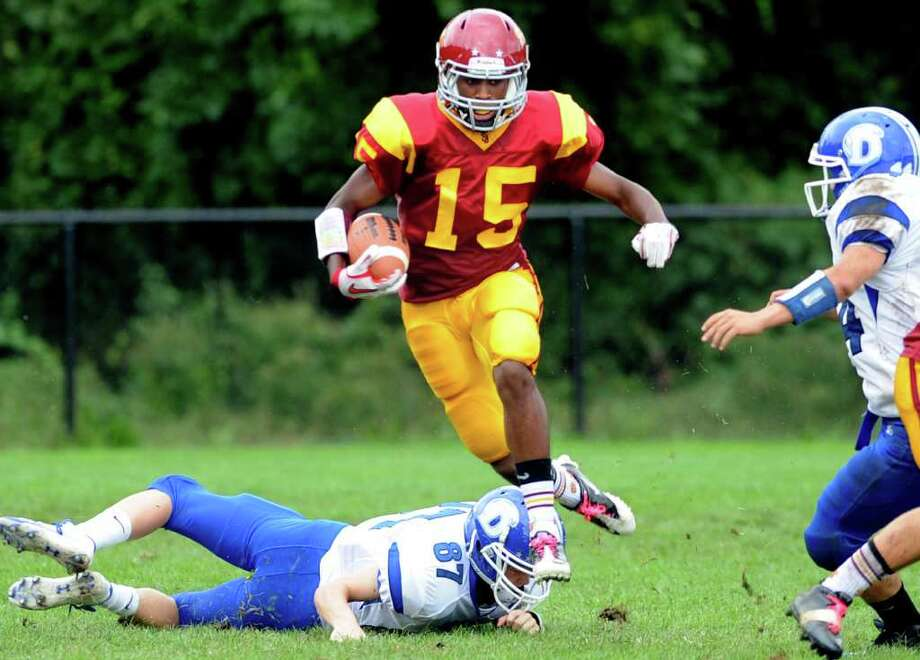 St. Joseph's Denzel Moscova runs past Darien's Jackson Whiting (87)during Saturday's game at the St. Joseph campus in Trumbull, Conn. Photo: Autumn Driscoll