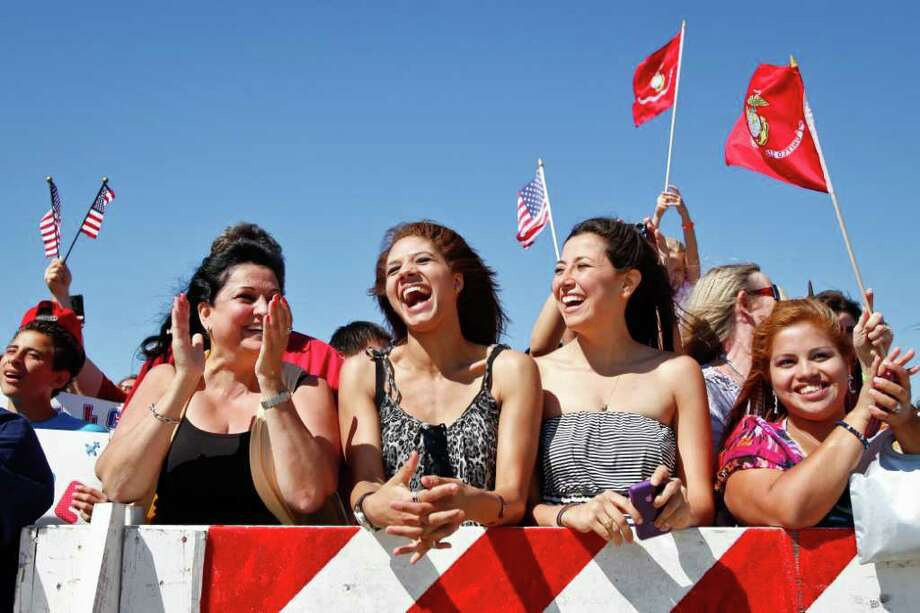 Alexandra Garcia, left, Leah Chatman and Carolina Garcia are among 1,000 people cheering as the Houston-based 1st Battalion, 23rd Marine Regiment arrives at Ellington Field. Photo: Michael Paulsen, Houston Chronicle / © 2011 Houston Chronicle