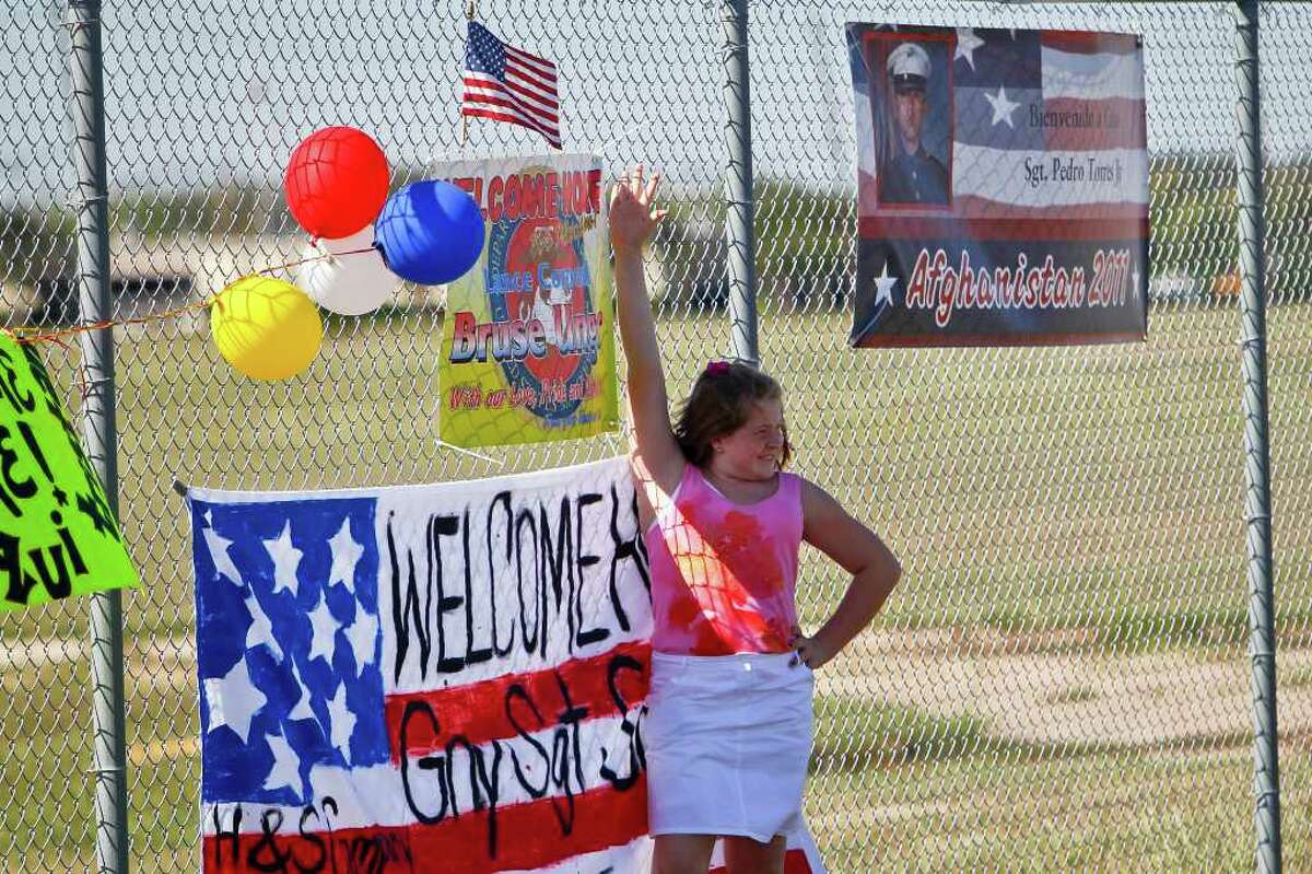 A young girl tries her hand at modeling as the crowd awaits the Marines' return.