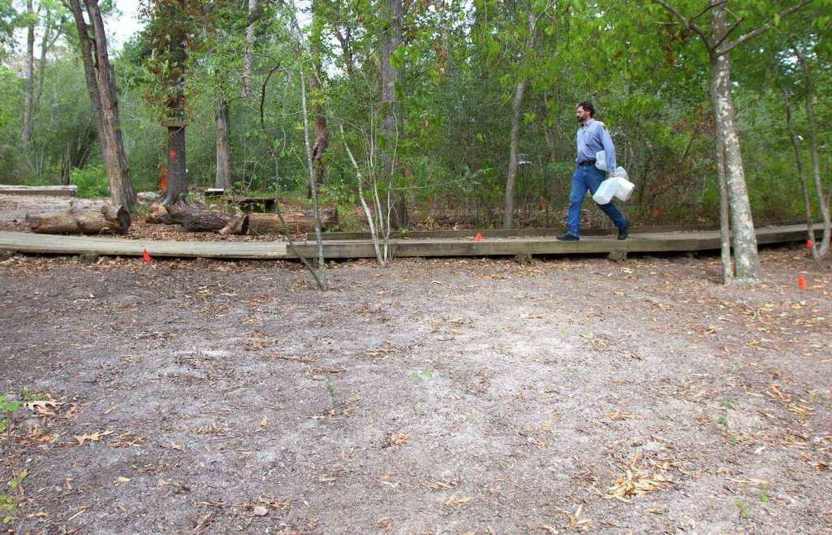 Blanton carries water jugs for a trail improvement project Thursday at the Houston Arboretum & Nature Center. Volunteers are clearing areas within 100 feet of walkways and buildings at the arboretum due to fire concerns.