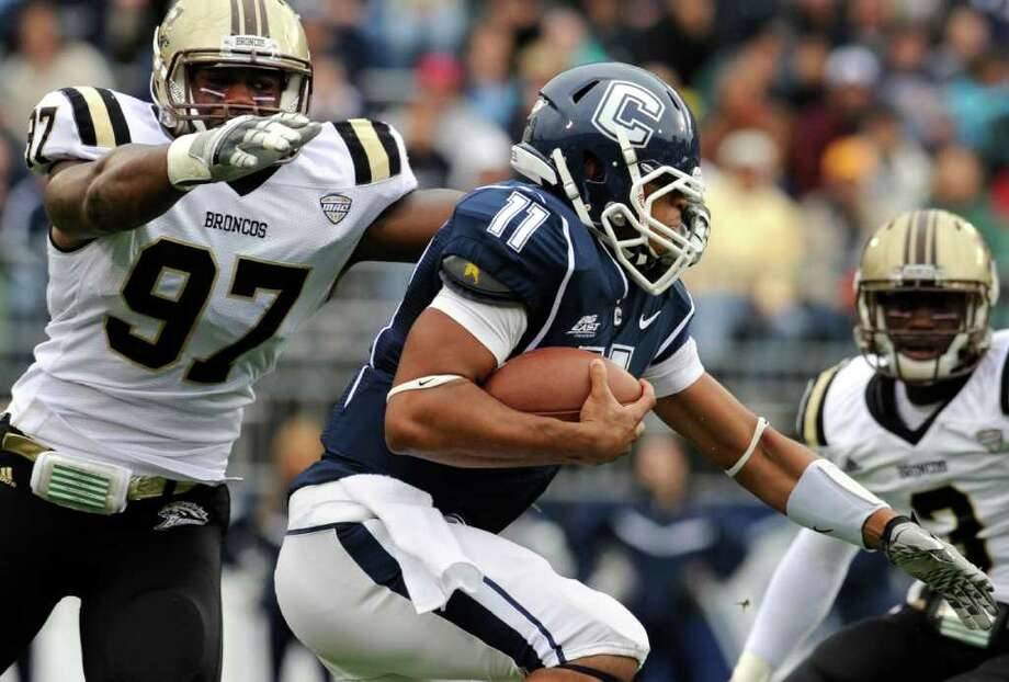 Connecticut quarterback Scott McCummings (11) runs the ball with pressure from Western Michigan's Freddie Bishop (97) in the first quarter of an NCAA college football game, in East Hartford, Conn., on Saturday, Oct. 1, 2011. (AP Photo/Jessica Hill) Photo: Jessica Hill/Associated Press / AP2011