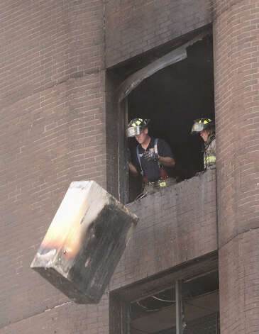 Firefighters toss a desk out of the broken window of a building that was damaged as a fire destroyed an adjacent building at the corner of Main and Commerce early on Saturday, Oct. 1, 2011. Photo: BILLY CALZADA/gcalzada@express-news.net