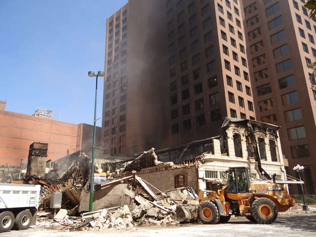 Workers clean up debris left by a fire that destroyed a historic building off of Main Plaza early on Saturday, Oct. 1, 2011. Photo: BILLY CALZADA/gcalzada@express-news.net