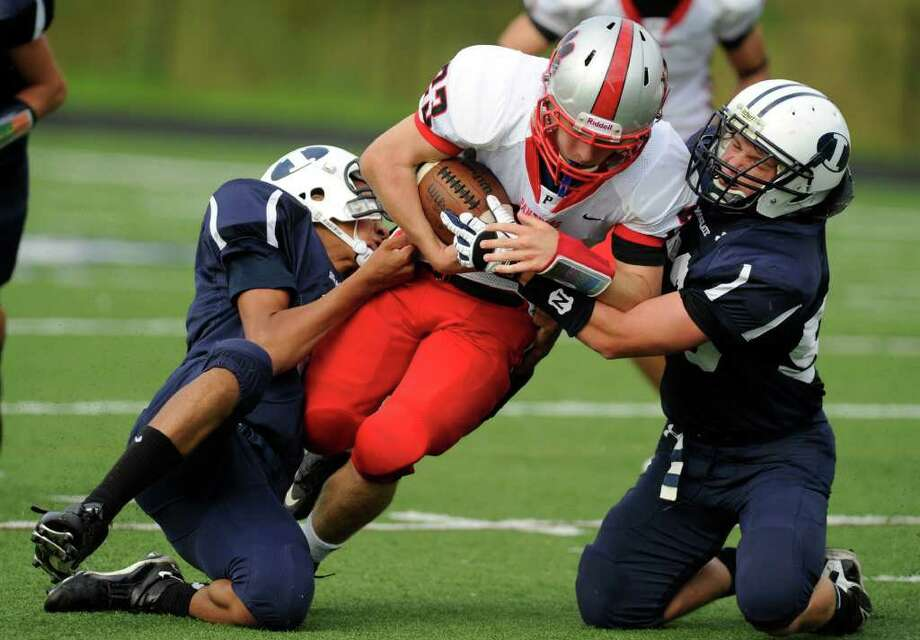 Pomperaug's Dylan McAllister, center, is brought down by Immaculate's Darel Bowman, left, and Nick Costa, right, during their game at Immaculate High School on Saturday, Oct. 1, 2011. Photo: Jason Rearick / The News-Times