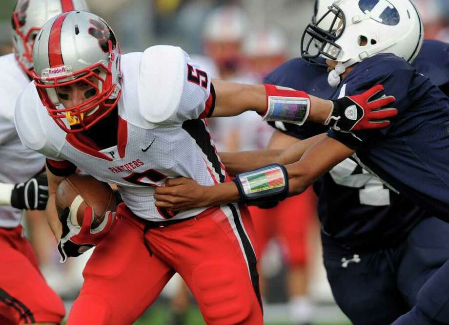 Pomperaug's Matt Paola, left, evades Immaculate's Darel Bowman during their game at Immaculate High School on Saturday, Oct. 1, 2011. Photo: Jason Rearick / The News-Times