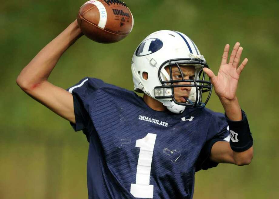 Immaculate's Darel Bowman winds back to throw during their game against Pomperaug at Immaculate High School on Saturday, Oct. 1, 2011. Photo: Jason Rearick / The News-Times