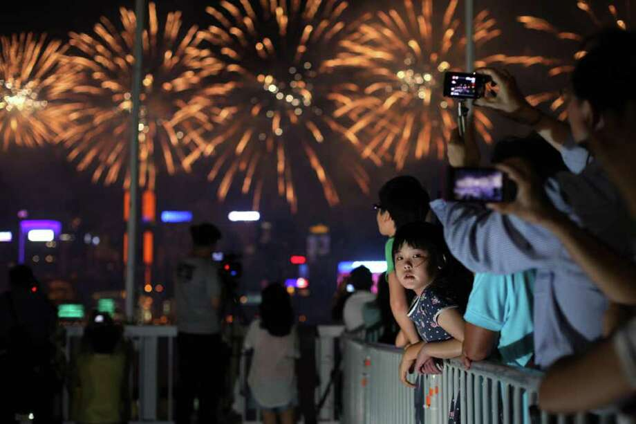 A girl watches as fireworks light up Victoria harbour and the Hong Kong skyline during National Day celebrations on October 1, 2011. China, together with Hong Kong and Macau, was celebrating its 62nd anniversary with a variety of government-organised festivities. Photo: ED JONES, Getty / AFP