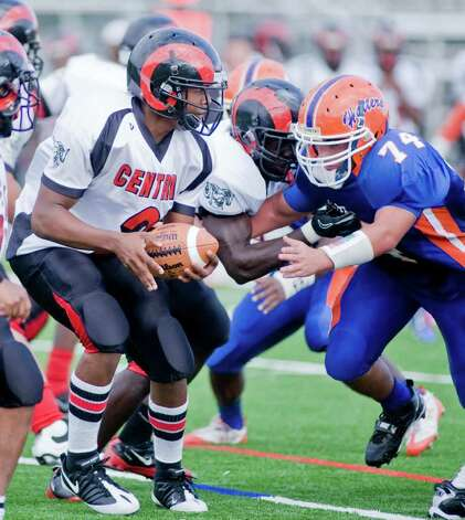 Bridgeport Central High School quarterback Xavier Hardison tries to avoid a rushing Tyler Hancock of Danbury High School in a football game at Danbury. Saturday, Oct. 1, 2011 Photo: Scott Mullin / The News-Times Freelance