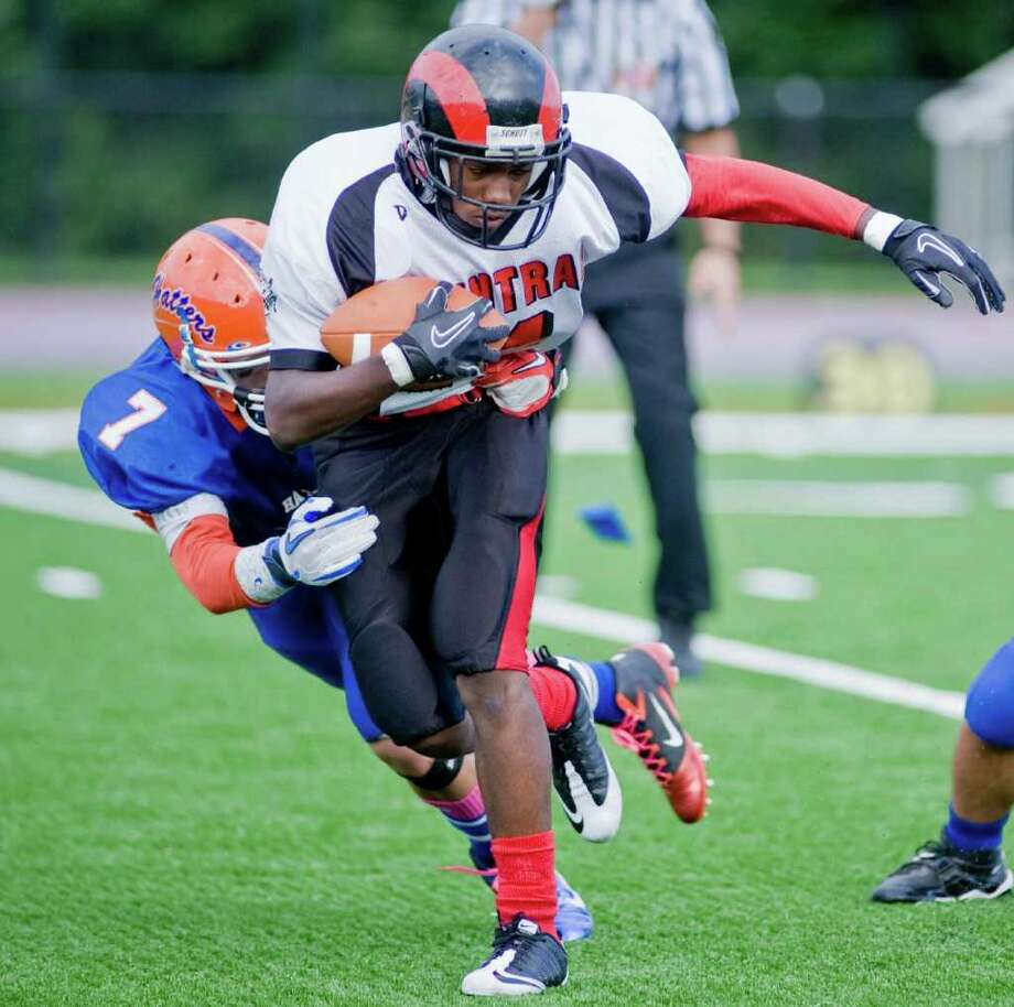 Danbury High School's Corey Chaffee grabs Bridgeport Central High School's Chad Lawrence in a football game at Danbury. Saturday, Oct. 1, 2011 Photo: Scott Mullin / The News-Times Freelance