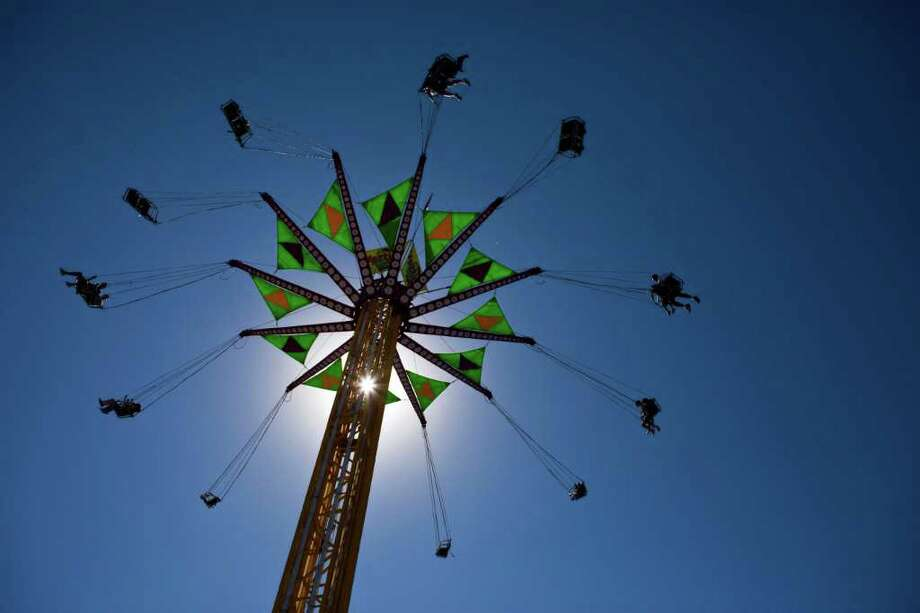 Riders swing around on the Vertigo on opening day of the State Fair of Texas. Photo: Patrick T. Fallon, Associated Press / The Dallas Morning News