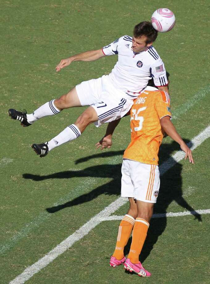 NICK de la TORRE: CHRONICLE AERIAL ACROBATS: Fire midfielder Victor Pineda and Dynamo forward Brian Ching contest a header during Saturday's MLS match at Robertson Stadium. Photo: Nick De La Torre / © 2011 Houston Chronicle