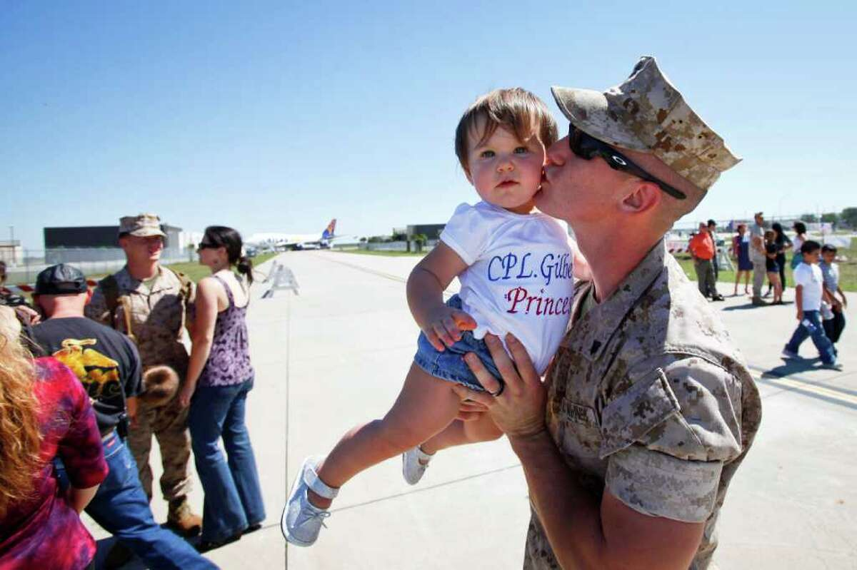 Cpl. Michael Gilbert kisses his daughter Kierstin, 1, at Ellington field on Saturday. Three-hundred and thirty-seven Marines returned home to Houston to cheers from an estimated 1,000.