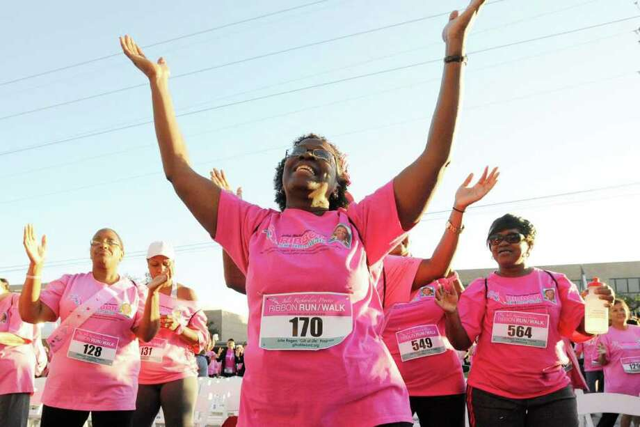 Race entrant Myrna Parker, of Port Arthur, center, enjoys the fun of a  Zumba warmup with other participants before the start of the Julie Richardson Procter 5K Ribbon Run/Walk in Downtown Beaumont on Saturday,  October 1, 2011.  Valentino Mauricio/The Enterprise