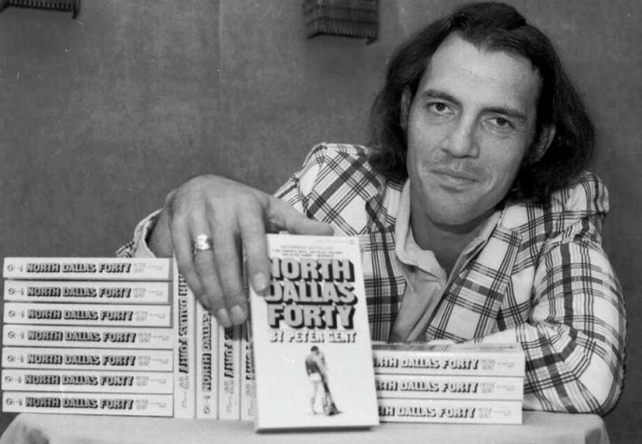 """FILE - In this Aug. 26, 1974 file photo, former Dallas Cowboys flanker, and author Peter Gent poses with copies of his bestseller """"North Dallas Forty,"""" in New York. Gent, whose book about the seamier side of football was made into a movie by the same name, has died in his native Michigan. D.L. Miller Funeral Home says Gent died Friday, Sept. 30, 2011, at age 69 in Bangor, where he grew up. No other details were immediately available. (AP Photo, File) / AP"""