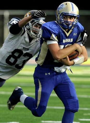 Weston's Matt Keeney reaches for Newtown quarterback Greg Frattaroli during their game at Newtown High School on Saturday, Oct. 1, 2011. Newtown beat Weston 41-7. Photo: Jason Rearick / The News-Times