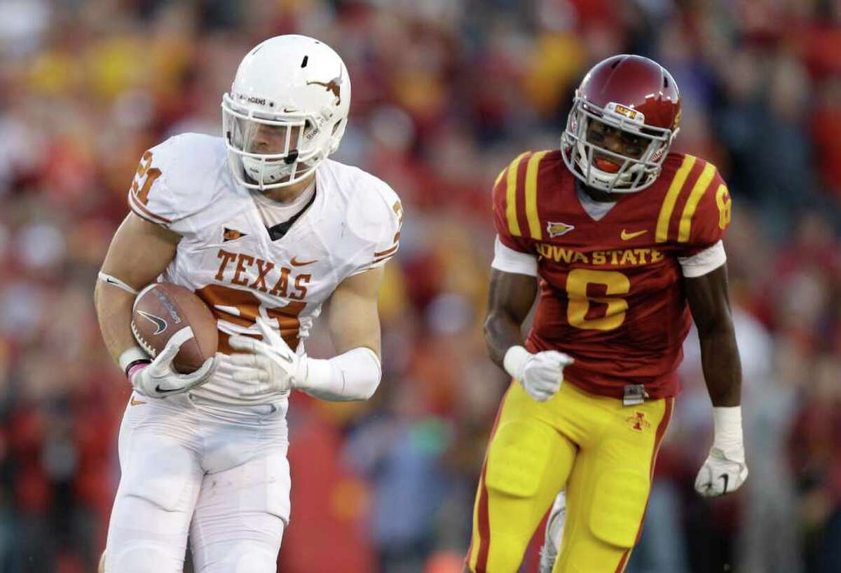 Texas safety Blake Gideon runs from Iowa State wide receiver Darius Darks, right, after intercepting a pass during the first half of an NCAA college football game Saturday, Oct. 1, 2011, in Ames, Iowa. (AP Photo/Charlie Neibergall)