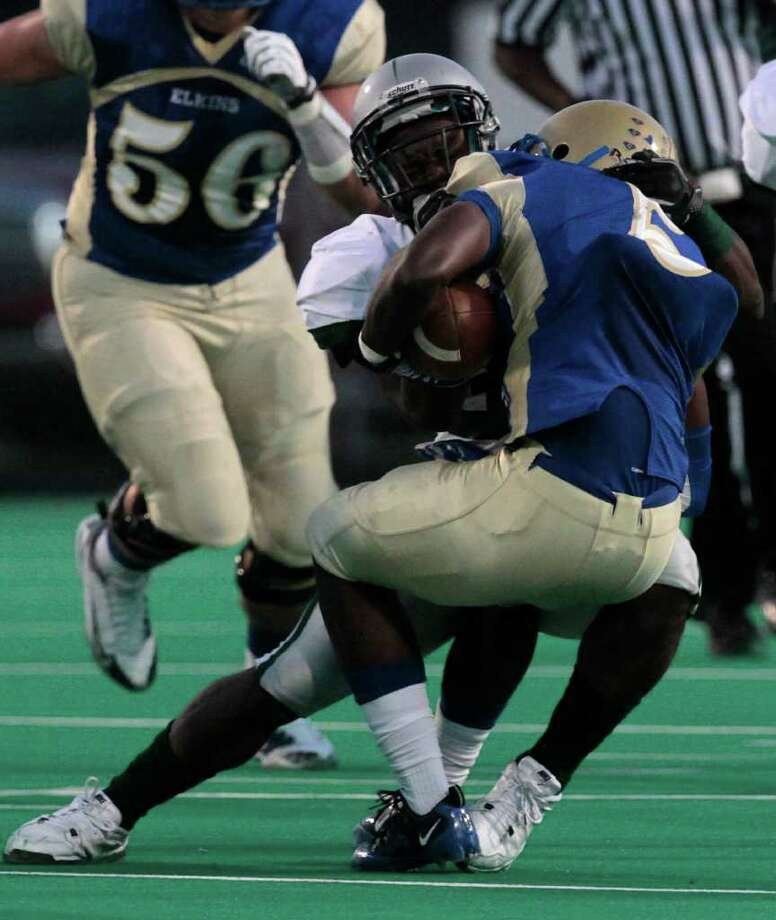 Elkins High School JaWuan Rogers (right) is brought down by Hightower High School's Joshua Price during the first quarter of a football game at Kenneth Hall Stadium Saturday, Oct. 1, 2011, in Missouri City. Photo: Cody Duty, Houston Chronicle / © 2011 Houston Chronicle
