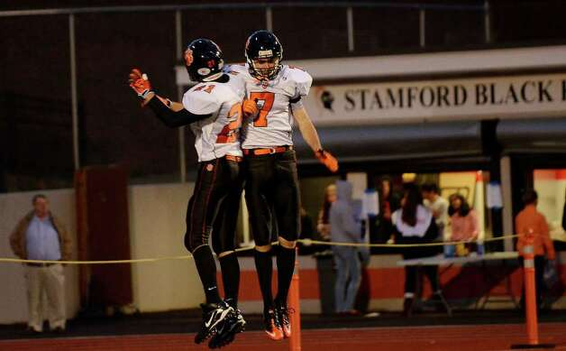 Ridgefield's #21 Neil Gollogly celebrates with teammate #7 John Heller after Heller scored a touchdown as Stamford High School hosts Ridgefield High School in varsity football action in Stamford, CT on Saturday, Oct. 1, 2011. Photo: Shelley Cryan / Shelley Cryan freelance; Stamford Advocate freelance