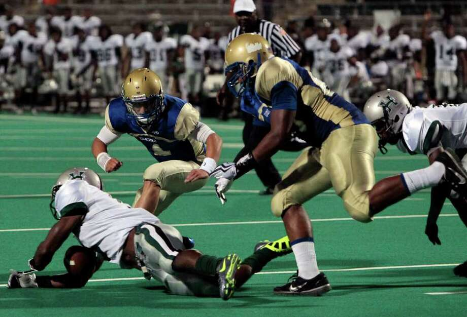Hightower High School's Myles Houston (left) recovers a fumble as he is pressured by Elkins High School quarterback Jake Burkhalter (center) and Tyler Scott (right) during the second quarter of a football game at Kenneth Hall Stadium Saturday, Oct. 1, 2011, in Missouri City. Photo: Cody Duty, Houston Chronicle / © 2011 Houston Chronicle