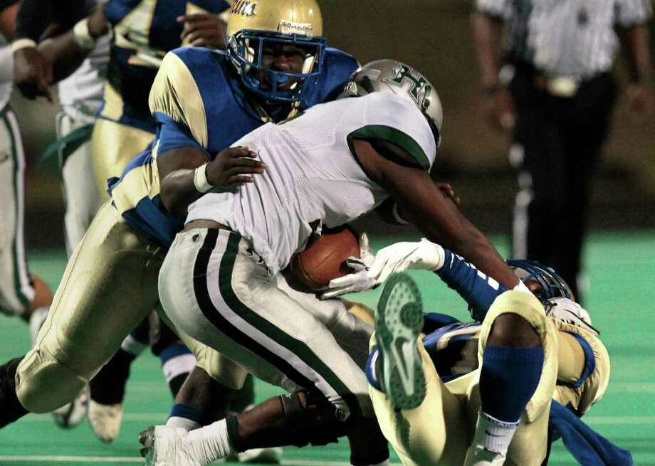 Hightower High School running back Joshua Wilhite (center) shakes off a tackle from Elkins High School's Corey Thompson (right) as Germay Morrisette (left) defends during the second quarter of a football game at Kenneth Hall Stadium Saturday, Oct. 1, 2011, in Missouri City.  (Cody Duty / Houston Chronicle)  51,3,7 Photo: Cody Duty, Houston Chronicle / © 2011 Houston Chronicle