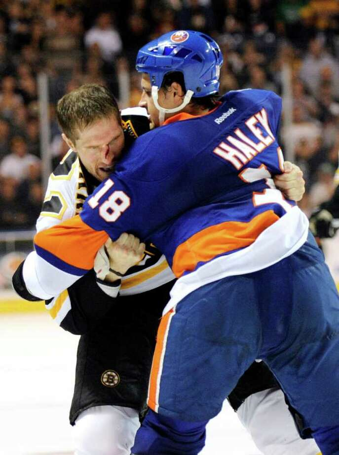 Boston Bruins' Chris Clark, left, fights with New York Islanders' Michael Haley (18) during the second period of a preseason NHL hockey game in Bridgeport, Conn., on Saturday, Oct. 1, 2011. The Bruins won the game 3-2. (AP Photo/Fred Beckham) Photo: Fred Beckham/Associated Press / FR153656 AP