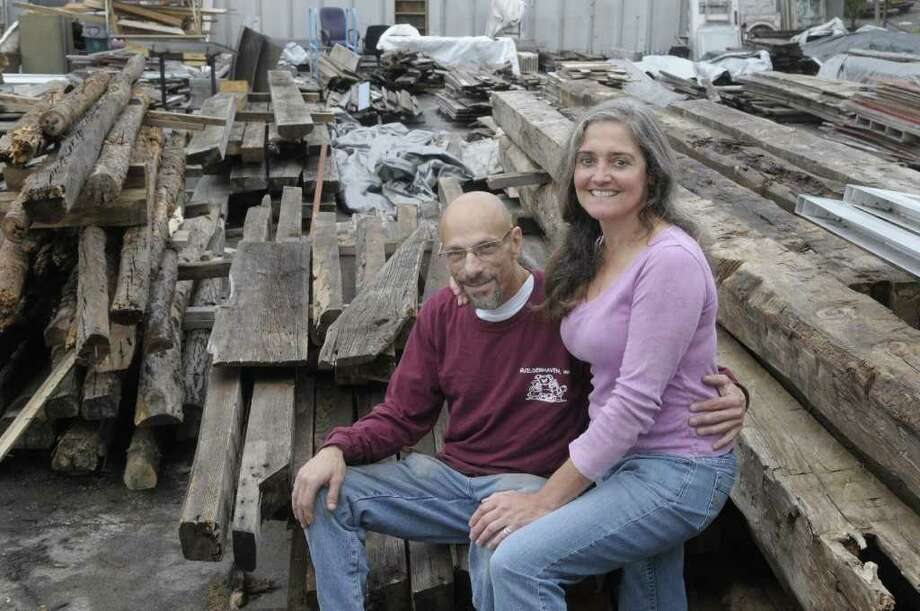 Fred Shapiro, left, and Camille Gibeau pose outside of Silver Fox Salvage with some of the salvaged wood that they use to make custom tabels on Wednesday, Sept. 21, 2011 in Albany.   (Paul Buckowski / Times Union) Photo: Paul Buckowski  / 00014709A