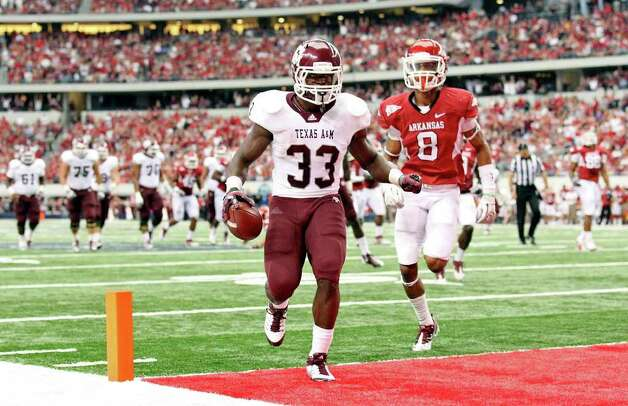 FOR SPORTS - Texas A&M's Christine Michael scores a touchdown ahead of Arkansas' Tevin Mitchel during first half action of the 2011 Southwest Classic Saturday Oct. 1, 2011 at Cowboys Stadium in Arlington, TX. (PHOTO BY EDWARD A. ORNELAS/eaornelas@express-news.net) Photo: EDWARD A. ORNELAS, SAN ANTONIO EXPRESS-NEWS / © SAN ANTONIO EXPRESS-NEWS (NFS)