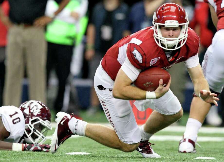 FOR SPORTS - Arkansas' Tyler Wilson falls after being tripped up by Texas A&M's Sean Porter during first half action of the 2011 Southwest Classic Saturday Oct. 1, 2011 at Cowboys Stadium in Arlington, TX. (PHOTO BY EDWARD A. ORNELAS/eaornelas@express-news.net) Photo: EDWARD A. ORNELAS, SAN ANTONIO EXPRESS-NEWS / © SAN ANTONIO EXPRESS-NEWS (NFS)