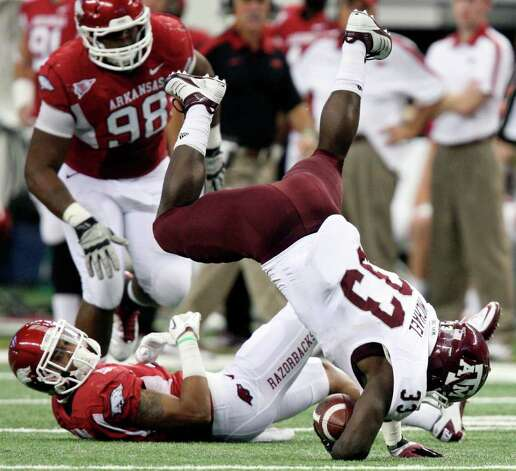FOR SPORTS - Texas A&M's Christine Michael comes down after leaping over Arkansas' Tramain Thomas  during first half action of the 2011 Southwest Classic Saturday Oct. 1, 2011 at Cowboys Stadium in Arlington, TX. (PHOTO BY EDWARD A. ORNELAS/eaornelas@express-news.net) Photo: EDWARD A. ORNELAS, SAN ANTONIO EXPRESS-NEWS / © SAN ANTONIO EXPRESS-NEWS (NFS)