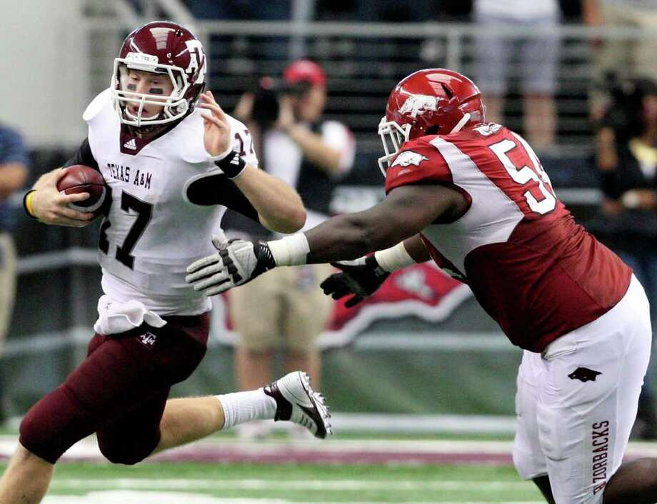 FOR SPORTS - Texas A&M's Ryan Tannehill looks for room around Arkansas' Byran  Jones during second half action of the 2011 Southwest Classic Saturday Oct. 1, 2011 at Cowboys Stadium in Arlington, TX. Arkansas won 42-38. (PHOTO BY EDWARD A. ORNELAS/eaornelas@express-news.net) Photo: EDWARD A. ORNELAS, SAN ANTONIO EXPRESS-NEWS / © SAN ANTONIO EXPRESS-NEWS (NFS)
