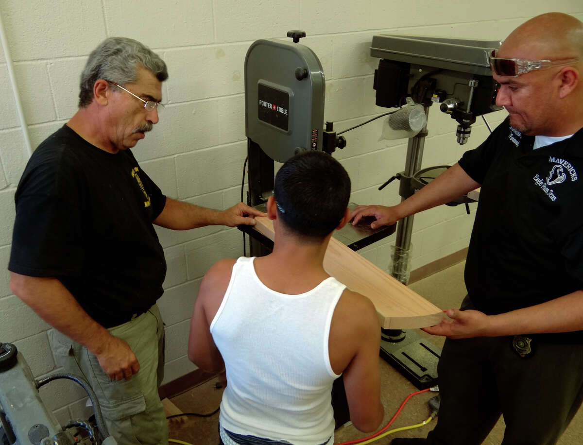 Bruce Ballou, chief probation officer of the juvenile probation department in Eagle Pass, left, and probation officer Eduardo Fernandez, right, teach woodworking to youth that have been in trouble with the law on Thursday, Sept. 22, 2011.