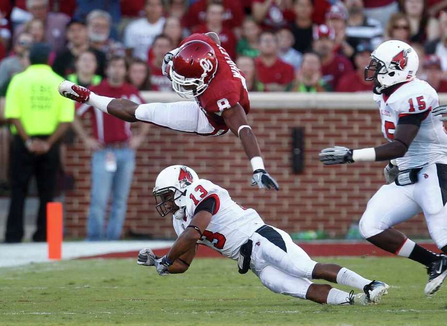 Oklahoma running back Dominique Whaley, top, flies over Ball State cornerback Armand Dehaney, bottom, after a tackle by Dehaney in the first quarter of an NCAA college football game in Norman, Okla., Saturday, Oct. 1, 2011. Ball State's Aaron Morris moves in at right. (AP Photo/Sue Ogrocki) Photo: Sue Ogrocki / AP