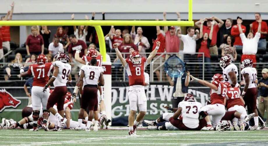 BRANDON WADE : ASSOCIATED PRESS Quarterback Tyler Wilson (8) and many Arkansas fans give the signal as Broderick Green scores on a 3-yard run with 1:41 remaining to finish a second half in which the Razorbacks outscored the Aggies 25-3. Photo: Brandon Wade / FR168019 AP