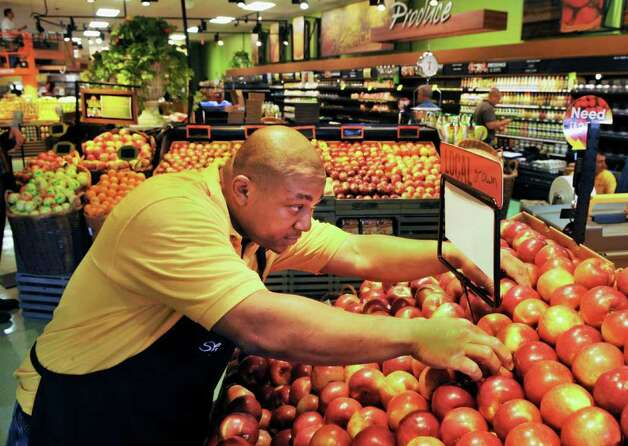 Produce associate Dino Ward of Schenectady preps a display of local apples at the new ShopRite store in Niskayuna Friday Sept. 30, 2011.   (John Carl D'Annibale / Times Union) Photo: John Carl D'Annibale / 00014816A