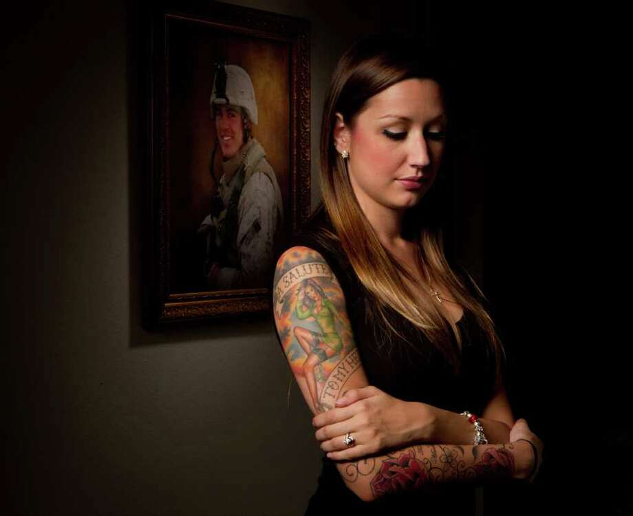 A portrait of Rachel Smith's late husband, Marine Staff Sgt. Jeremy Smith, who was killed in Afghanistan in April, hangs in her Fort Worth home. The tattoos on her arm are a tribute to their love and his life as a Marine. Photo: Billy Smith II / © 2011 Chronicle