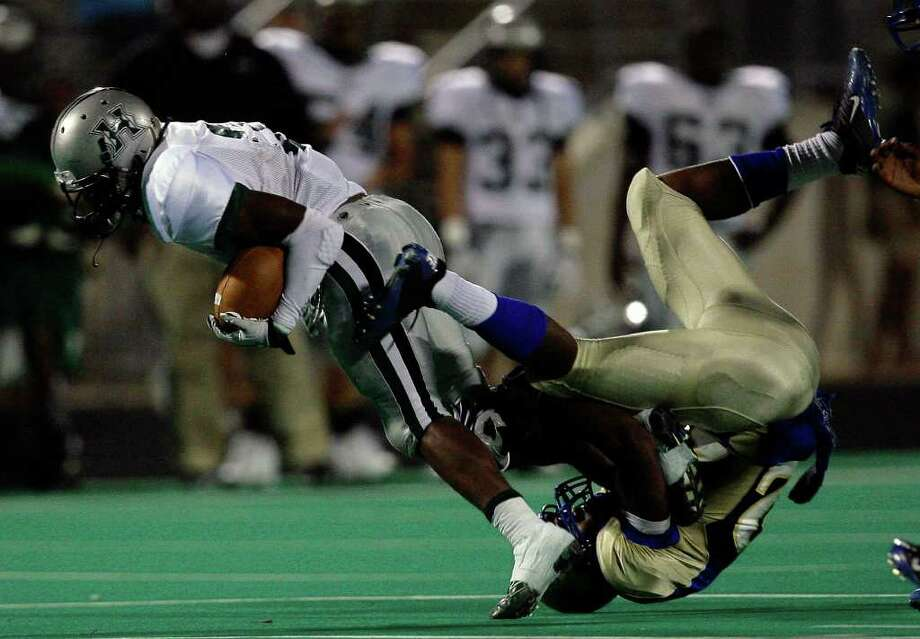 CODY DUTY: CHRONICLE UPENDED: Hightower's Joshua Wilhite shakes off a tackle from Elkins' Kamane Thomas in Saturday's District 23-5A game. Wilhite rushed for 178 yards and scored on a 3-yard run. Photo: Cody Duty / © 2011 Houston Chronicle