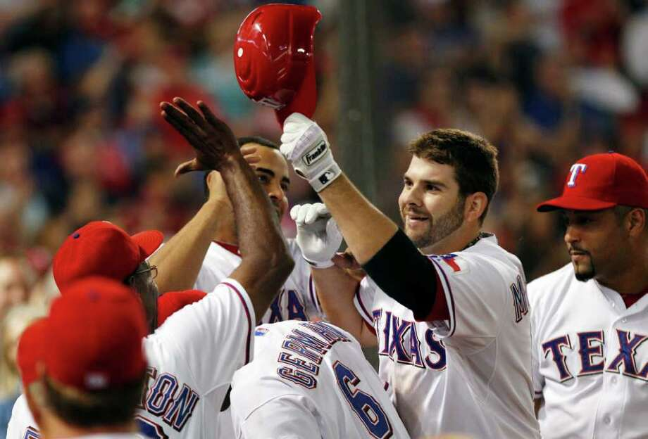LM OTERO: ASSOCIATED PRESS FINISHING TOUCH: Mitch Moreland, right, works the receiving line after his bases-empty homer put the Rangers ahead of the Rays by two runs in the eighth inning. Photo: LM Otero / AP