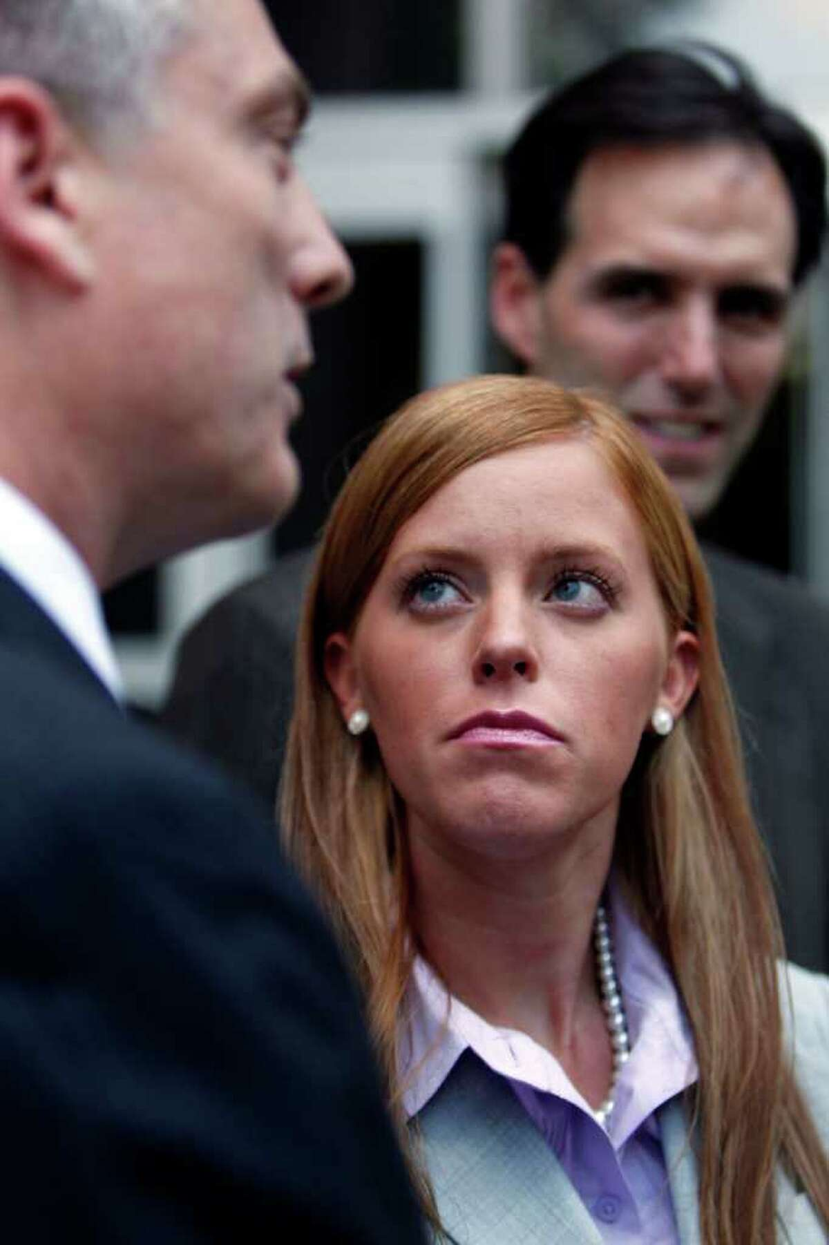 Next to her attorneys Todd Kelly (left) and Ron Estefan (right), Jamie Leigh Jones,who said she was raped while working for KBR, a Halliburton subsidiary, in Iraq in 2005 watches Kelly speak to the media outside the Bob Casey Federal Courthouse as her civil trial against the company began Tuesday, June 14, 2011, in Houston. Jones said she was drugged and sexually assaulted by her co-workers. ( Johnny Hanson / Houston Chronicle )