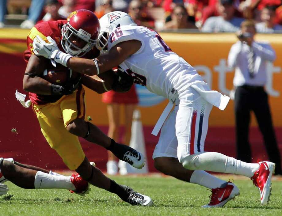 DANNY MOLOSHOK: ASSOCIATED PRESS TROJANS' HORSE: Southern Cal's Robert Woods, making a catch against Arizona's Jourdon Grandon, teamed up with quarterback Matt Barkley for more eye-popping numbers in a 48-41 win over the Wildcats. Woods caught 14 passes for 255 yards and two touchdowns. Barkley broke Carson Palmer's 2002 school record with 468 passing yards while throwing for four touchdowns. Photo: Danny Moloshok / FR161655 AP