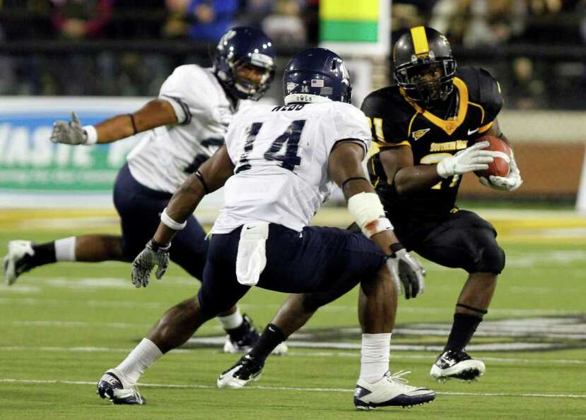 Southern Mississippi running back Jeremy Hester (21) tries to dodge Rice safety Xavier Webb (14) in