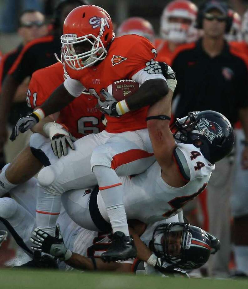 Sam Houston's Tim Flanders (20) is pulled down for a loss by UTSA's Steven Kurfehs (44) during the first half of a college football game, Saturday, October 1, 2011 at Bowers Stadium in Huntsville, TX. Photo: Eric Christian Smith, For The San Antonio Express-News