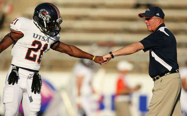 UTSA head coach Larry Coker greets Chris Johnson (21) during warmups before the Roadrunners' game against Sam Houston, Saturday, October 1, 2011 at Bowers Stadium in Huntsville, TX. Photo: Eric Christian Smith, For The San Antonio Express-News