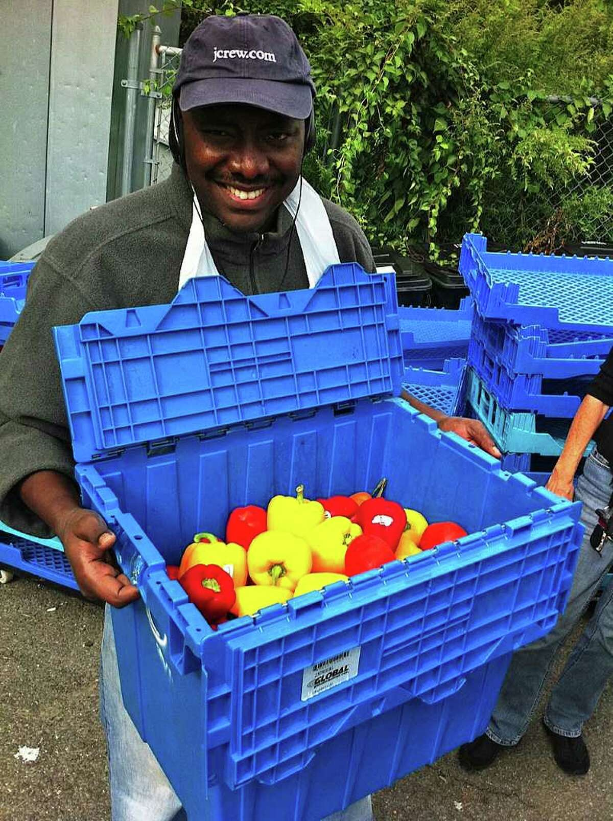 Rafael Arpacio, an employee at Stamford's New Covenant House, looks over some fresh produce delivered by Community Plates volunteers.