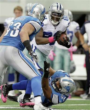 Dallas Cowboys wide receiver Dez Bryant takes the ball down field as Detroit Lions defensive end Kyle Vanden Bosch, left, and DeAndre Levy bottom defend during the first quarter of an NFL football game Sunday, Oct. 2, 2011, in Arlington, Texas. (AP Photo/Tony Gutierrez) Photo: Tony Gutierrez, Associated Press / AP
