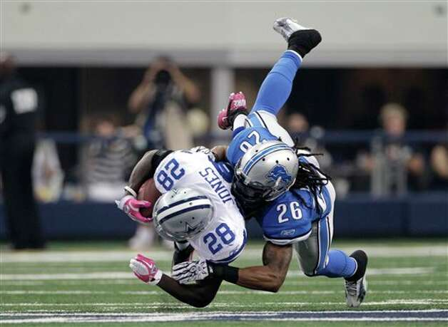 Detroit Lions free safety Louis Delmas (26) brings down Dallas Cowboys running back Felix Jones (28) in the first half following a long run an NFL football game Sunday, Oct. 2, 2011, in Arlington, Texas. (AP Photo/Tony Gutierrez) Photo: Tony Gutierrez, Associated Press / AP