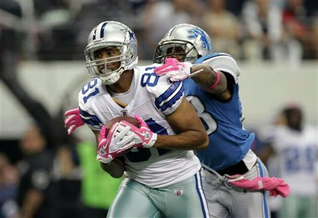 Dallas Cowboys tight end Jason Witten (82) attempts to escape a tackle by Detroit Lions cornerback Chris Houston, right, following a reception by Robinson in the first half of an NFL football game Sunday, Oct. 2, 2011, in Arlington, Texas. (AP Photo/Tony Gutierrez Photo: Tony Gutierrez, Associated Press / AP