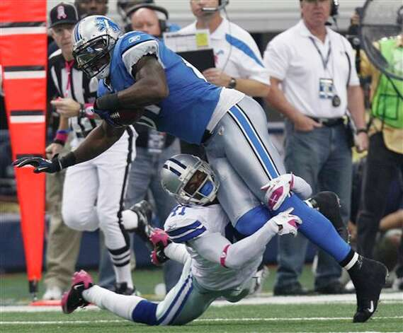 Detroit Lions wide receiver Calvin Johnson is tackled by Dallas Cowboys cornerback Terence Newman during the first half of an NFL football game Sunday, Oct. 2, 2011, in Arlington, Texas. (AP Photo/LM Otero) Photo: LM Otero, Associated Press / AP