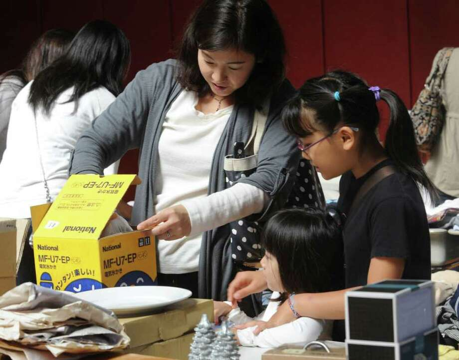 Yasuyo Kagawa shopping with her daughters Naho, 4, and Riho, 8, at the Greenwich Japanese School Parent Teacher Association's Bunka Festival at the school on Sunday, Oct. 2, 2011. Photo: Helen Neafsey / Greenwich Time